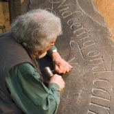 Ieuan carving text onto a boulder.