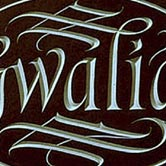 House name carved onto oval name plate with flowing details.