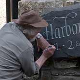 Ieuan adding the finishing touches to a house sign.