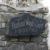 House sign mounted to a stone wall.